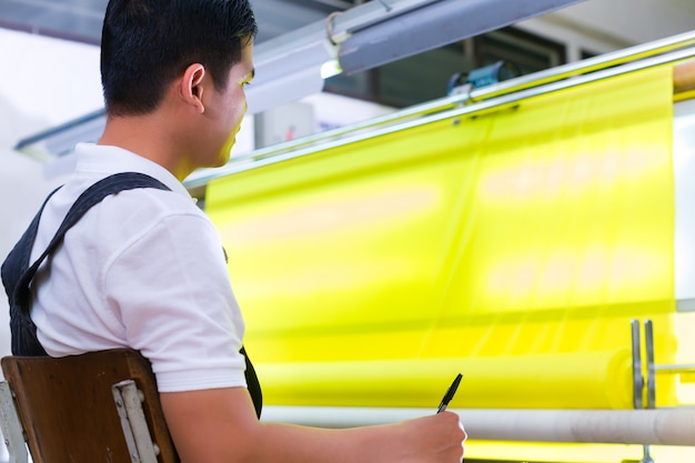 Asiatische arbeitskraft steuert gewebe in der textilfabrik