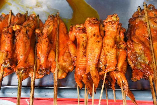 Asiatische art grillte hühnerflügel auf hölzernem hintergrund des behälters - thailändische brathähnchenaufsteckspindelnstöcke