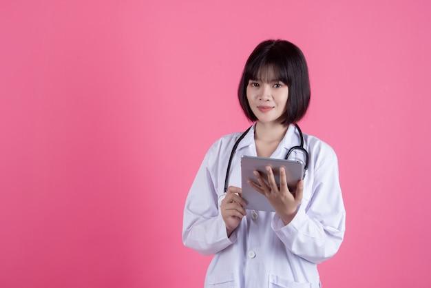 Asiatische arztfrau mit weißem laborkittel über rosa