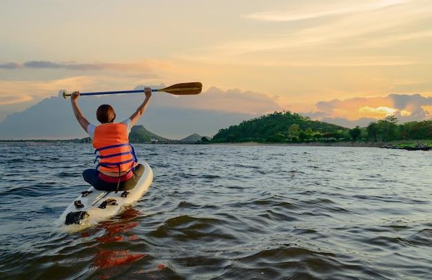 Asiatische athletische frau auf standpaddelbrett im see. solo outdoor sup aktivität und wassersport im sommerurlaub.