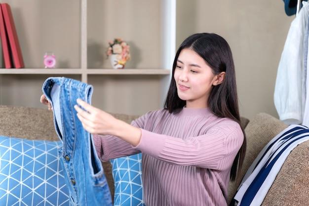 Asiatische attraktive frau, die zur neuen kleidung mit dem lächeln schaut