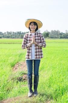 Asiatische bäuerin, die steht und die hände an der brust oder an der stirn im zeichen des respekts an der reisfarm zusammenpresst