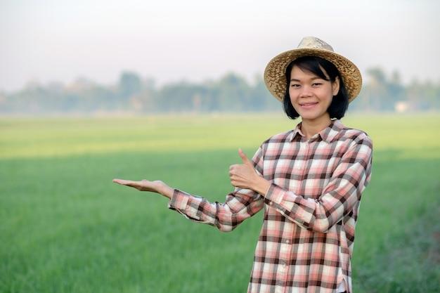 Asiatische bäuerin lächelt und posiert mit dem daumen nach oben auf einer grünen reisfarm