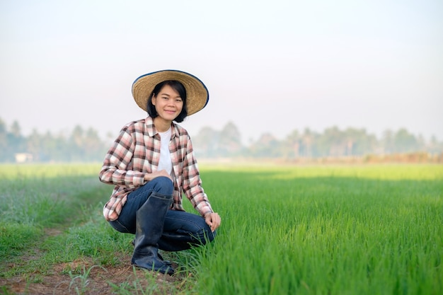 Asiatische bäuerin mit hut, die auf einer grünen reisfarm sitzt