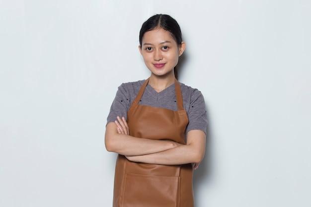 Asiatische barista-abnutzungsschürze verschränkte ihre arme café-service-konzept