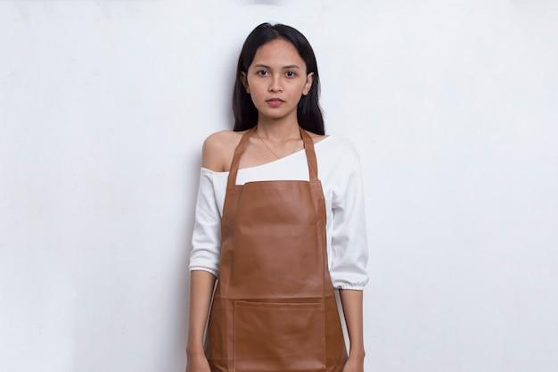 Asiatische barista-kellnerin mit schürze auf weißem hintergrund