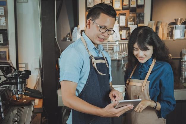 Asiatische baristas, die eine bestellung durch digitale tablette nehmen