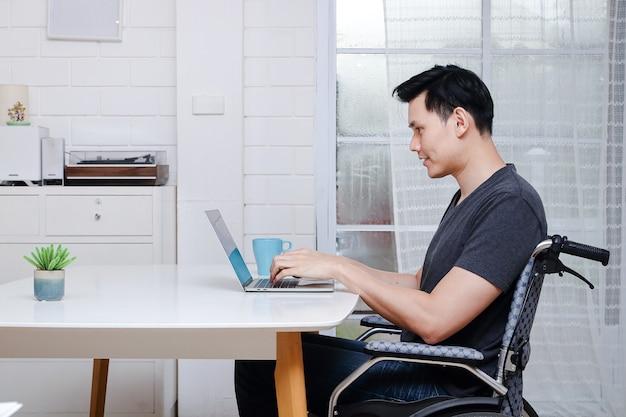 Asiatische behinderte männer in einem rollstuhl, der an einem laptop arbeitet