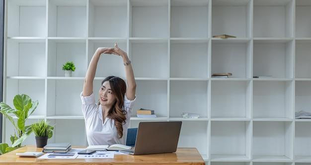Asiatische berufstätige frau, die sich entspannt, eine geschäftsfrau im büro, sie entspannt sich, nachdem sie lange hart gearbeitet hat, wodurch müdigkeit und stress eine pause machen, sie hat das bürosyndrom. konzept für harte arbeit.