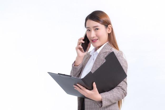 Asiatische berufstätige frau in formellem anzug mit weißem hemd ruft telefon an und öffnet dokumentdatei oder zwischenablage, um daten zu überprüfen.