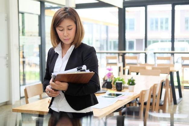 Asiatische berufstätige frau mit klemmbrett- und dokumentenpapier im büro.