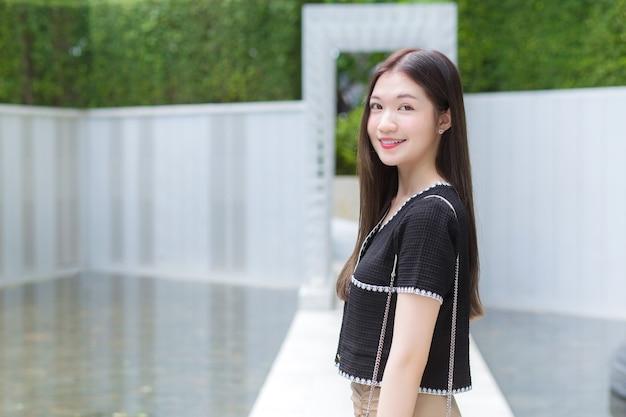 Asiatische berufstätige frau mit langen haaren in einem schwarzen hemd lächelt glücklich beim spaziergang im park.