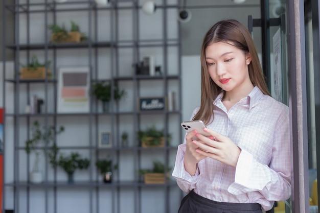 Asiatische berufstätige frauen verwenden smartphone, um mit jemandem in der digitalisierung zu chatten und von zu hause aus zu arbeiten.