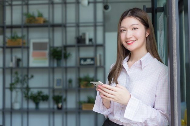 Asiatische berufstätige verwendet smartphone, um mit jemandem in der digitalisierung und arbeit zu chatten