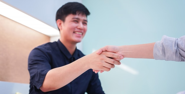 Asiatische bewerbermannhand, die mit manager nach abgeschlossenem vertrag im privaten konferenzsaal rüttelt
