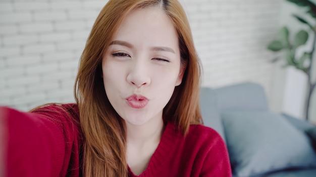Asiatische bloggerfrau, die zu hause smartphone, der vlog video im wohnzimmer aufnimmt