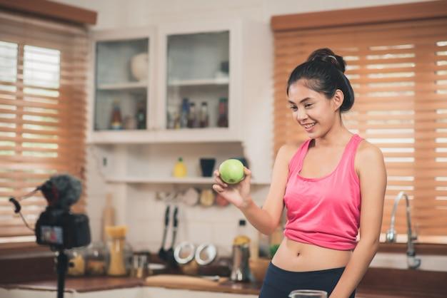Asiatische bloggerfrau machen vlog, wie man nährt und gewicht verliert, junge frau, die kameraaufnahme verwendet