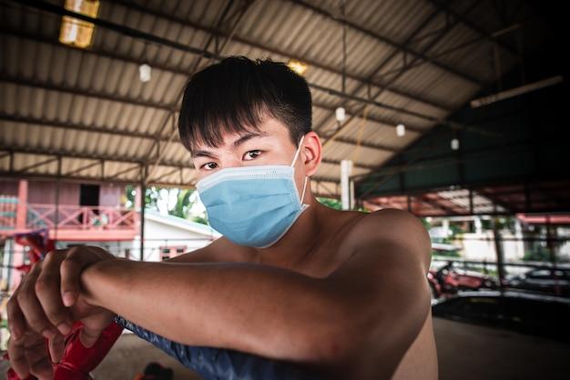 Asiatische boxer, die eine gesichtsmaske tragen. coronavirus krankheit