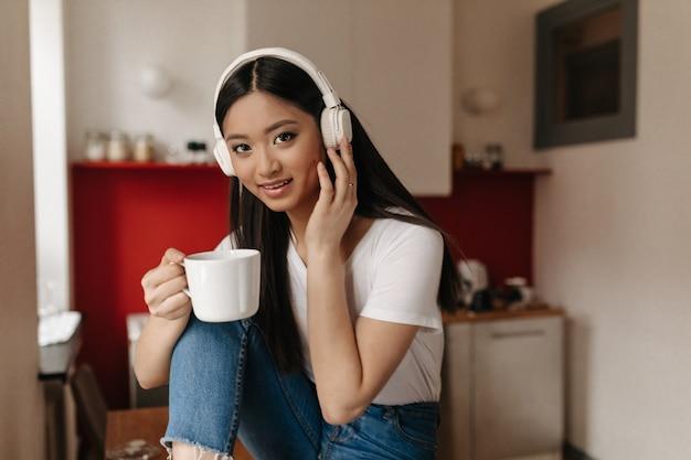 Asiatische braunäugige frau, die tasse tee auf hintergrund der küche hält