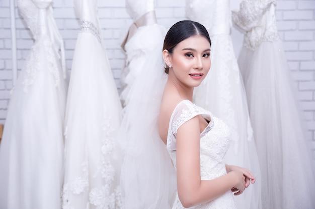 Asiatische braut der jungen frau, die auf hochzeitskleid an der modernen hochzeit versucht