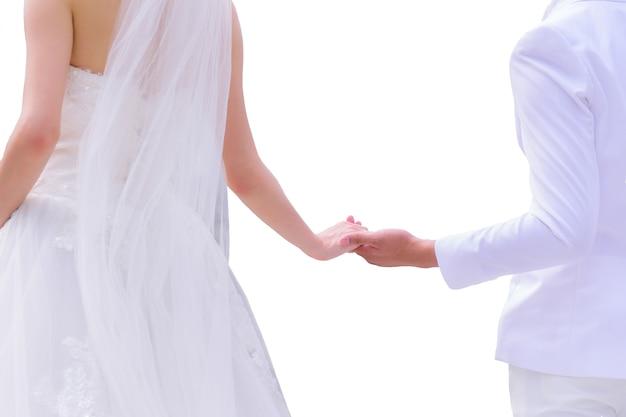 Asiatische braut im weißen hochzeitskleid und bräutigam im weißen anzug, der hände lokalisiert auf weißer wand hält