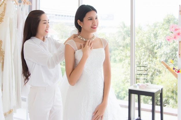 Asiatische braut thailänder wählen brautkleider und accessoires im laden aus, vermieten kleider und lassen sich schneiden, während der besitzer lächelt und glücklich ist