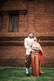 Asiatische braut und kaukasischer bräutigam haben romantische zeit mit thailand-kleid