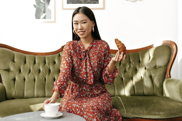 Asiatische brünette attraktive frau in stilvollem rotem blumenkleid lächelt aufrichtig, sitzt auf einem weichen grünen sofa, nimmt eine tasse tee und hält croissantis