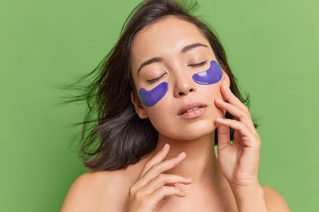 Asiatische brünette frau kümmert sich um zarten teint steht mit geschlossenen augen trägt hydrogel-patches auf, posiert für schönheitsbehandlungen gegen grüne wand