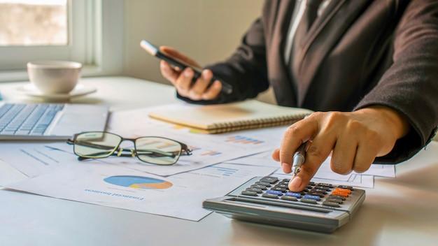 Asiatische buchhalter verwenden taschenrechner, um unternehmensbudgets, finanzideen und finanzbuchhaltung zu berechnen.