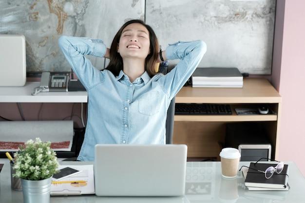 Asiatische bürofrau, die körper für das entspannen beim arbeiten mit laptop-computer an ihrem schreibtisch ausdehnt