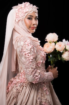 Asiatische charmante muslimische arabische braut in lace bead embroidery sweet pink altes rosenhochzeitskleid und hijab-kopftuch, nahaufnahme auf fashion make-up eyes face, studiobeleuchtung schwarzer hintergrund isoliert.