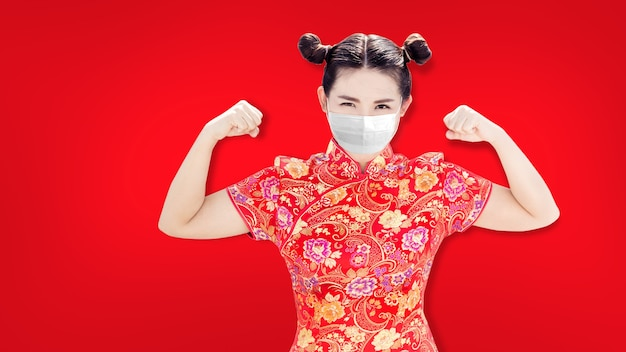 Asiatische chinesin auf roter sheongsam-tradition chiness-suite mit starker gesunder aktion mit gesichtsmaske bei coronavirus-pandemie