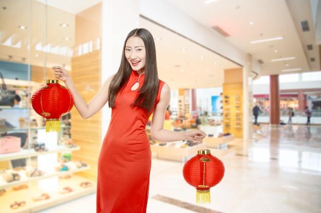Asiatische chinesin in einem cheongsam kleid, das chinesische laterne hält