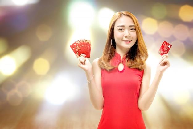 Asiatische chinesin in einem cheongsam kleid, das eine kreditkarte und roten umschläge hält