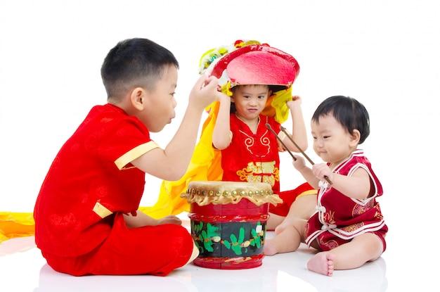 Asiatische chinesische kinder im traditionellen chinesischen cheongsam chinesisches neues jahr feiernd, lokalisiert auf weißem hintergrund.