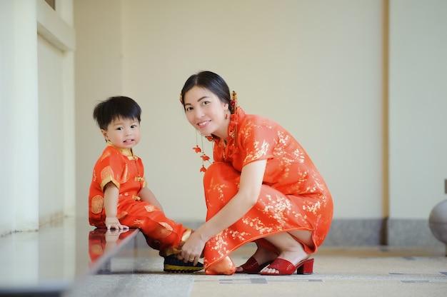 Asiatische chinesische kinderferien auf dem chinesischen neujahrsfest im chinesischen tempel mit traditionellem cheongsam.