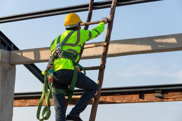 Asiatische dachbauarbeiter tragen sicherheitshöhenausrüstung, die die treppe hinaufgeht, um den dachrahmen zu installieren. absturzsicherungsvorrichtung für arbeiter mit haken für sicherheitsgurt auf der baustelle.