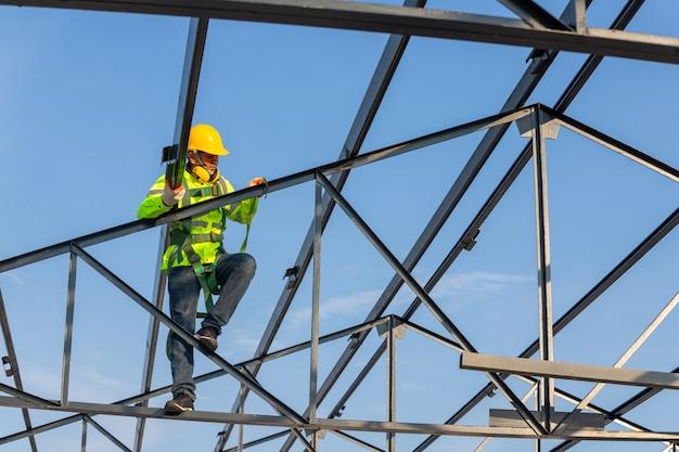 Asiatische dachbauer tragen sicherheitshöhenausrüstung, um den dachrahmen zu installieren. absturzsicherungsvorrichtung für arbeiter mit haken für sicherheitsgurte auf der baustelle.