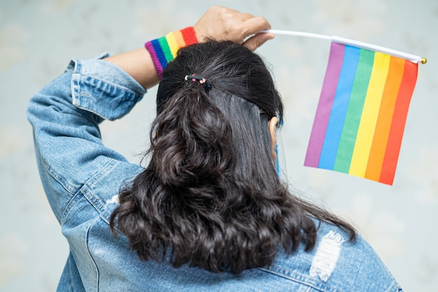 Asiatische dame, die blaue jeansjacke oder jeanshemd trägt und regenbogenfarbflagge hält.