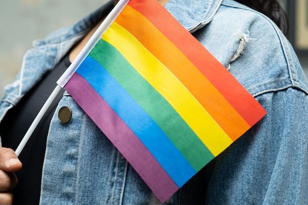 Asiatische dame, die blaue jeansjacke trägt und regenbogenfahne hält.