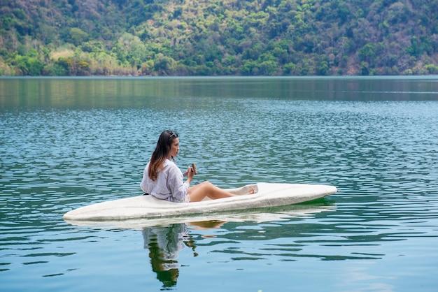 Asiatische dame, die den kajak auf dem see in satonda island schaufelt