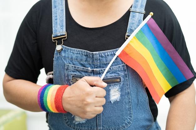 Asiatische dame, die eine blaue jeansjacke oder ein jeanshemd trägt und eine regenbogenfahne hält, das symbol des lgbt-stolzmonats, feiert im juni jährlich die sozialen, schwulen, lesbischen, bisexuellen, transgender, menschenrechte.