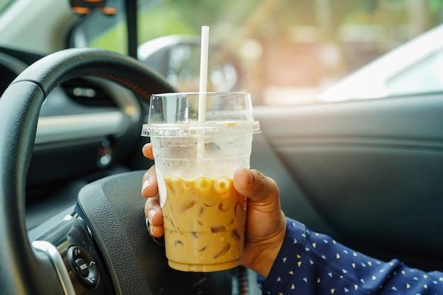 Asiatische dame, die eiskaffee am auto hält.