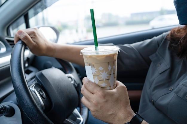 Asiatische dame, die eiskaffee im auto gefährlich hält und einen unfall riskiert.