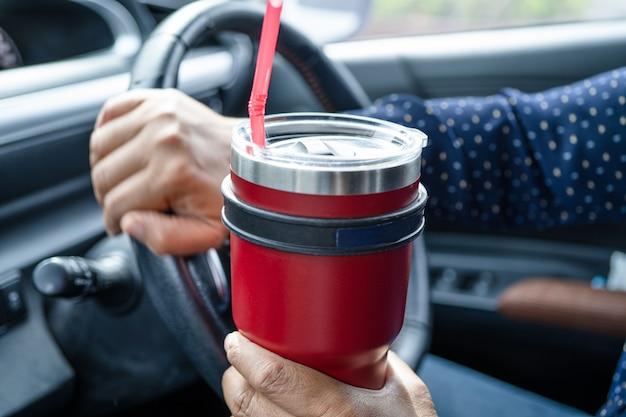 Asiatische dame, die eiskaffee im auto hält, gefährlich und riskiert einen unfall.