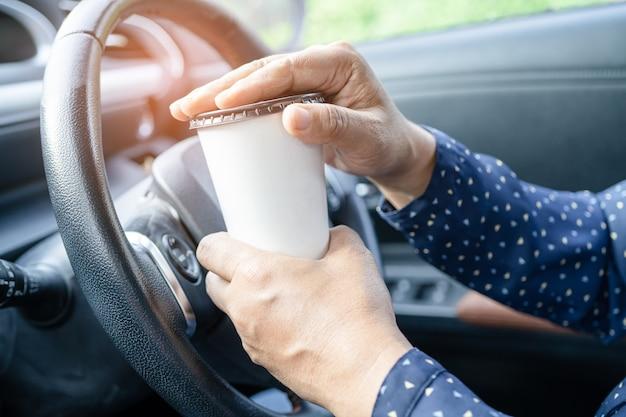 Asiatische dame, die kaffeetasse zum trinken im auto hält, gefährlich und riskiert einen unfall.