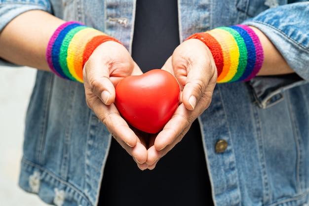 Asiatische dame, die regenbogenarmbänder trägt und rotes herz hält, symbol des lgbt-stolzmonats.