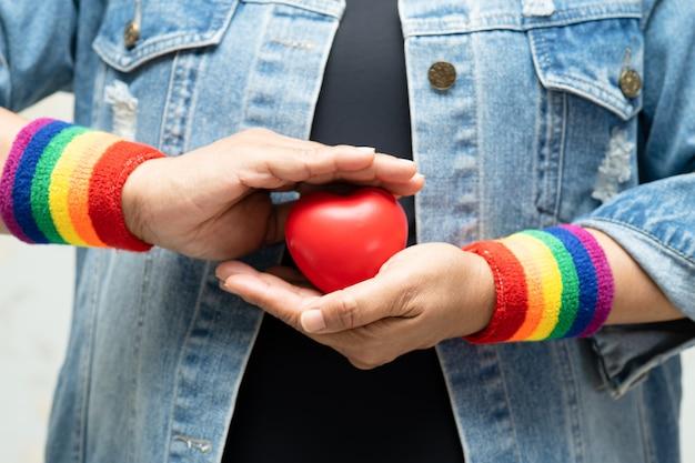 Asiatische dame, die regenbogenarmbänder trägt und rotes herz hält