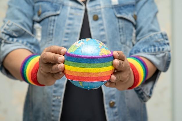 Asiatische dame, die regenbogenfarbflagge mit globus hält.